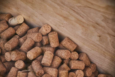 Many wine bottle corks in a wooden box. Selective focus and bokeh.