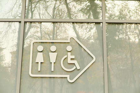Disabled sign and arrow on glass doors