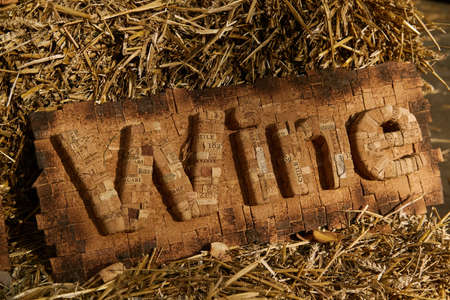 The inscription WINE made of corks from wine bottles. Around the inscription lies straw Zdjęcie Seryjne