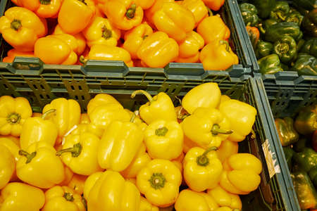 Lots of yellow and orange bell peppers in boxes in a supermarket Stock Photo
