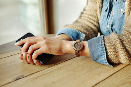A woman sits at a table with phones in her hands. A wrist watch is worn on the wrist. The face is not visible. Woman is waiting for someone. concept of being late