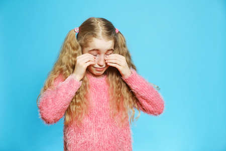 The little blond-haired girl cries, wiping her face with her hands. Isolated half-length portrait on a blue background