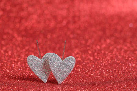 Two silver hearts on a red bokeh background. Hearts are pierced to the background with needles. Picture for Valentine's Day and wedding. Bokeh red color background.
