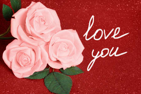 Valentines day card with three pink Roses on red boke Background. Love and Wedding Day concept. Card valentine day roses text.