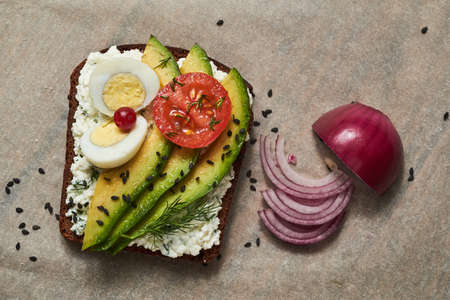Healthy toast with cottage cheese, avocado, egg and tomato. Nearby lies a purple chopped onion. A rustic sandwich.