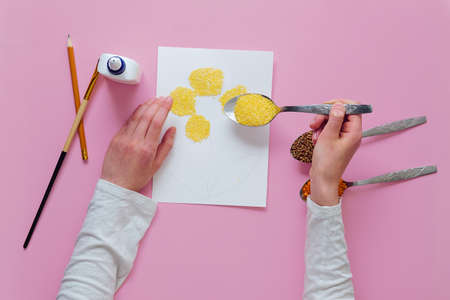 Instructions for making a kids craft. Step 4 - carefully pour the groats over the entire drawing. The concept of development of fine motor skills.