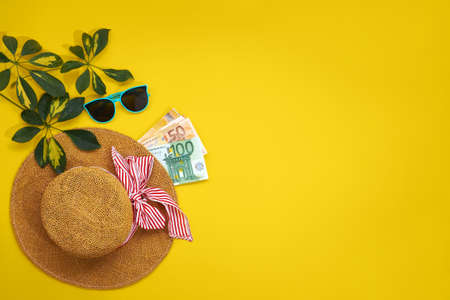 Accessories for the beach season and euro bills. Straw hat, sunglasses and leaves sheflers isolated on a yellow background. copy space