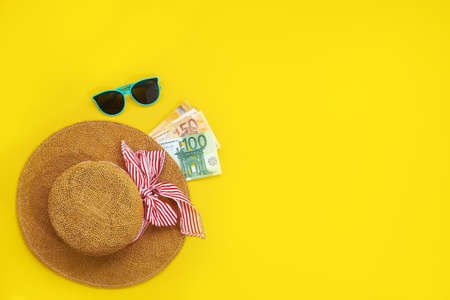 Straw hat with euro bills isolated on a yellow background. Top view flat lay. vacation cash expense concept Stock fotó