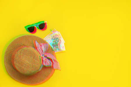 Straw hat with euro bills isolated on a yellow background. Top view flat lay. vacation cash expense concept. Glitch style effect.