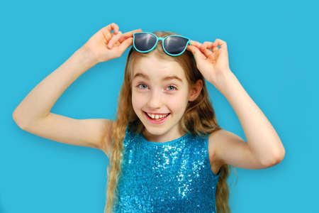Beautiful cheerful caucasian little girl holding sunglasses and looking at the camera. The girl is dressed in a beautiful blue dress. The concept of emotions and facial expressions.