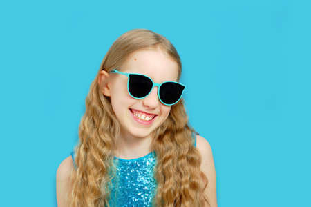 Beautiful little caucasian girl in sunglasses in a blue dress. The girl smiles and looks into the camera. Isolated half-length portrait on a blue background.