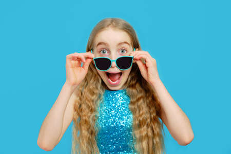 Beautiful naughty Caucasian little girl has taken off her sunglasses and is looking into the camera. The girl is dressed in a beautiful blue dress. The concept of emotions and facial expressions.