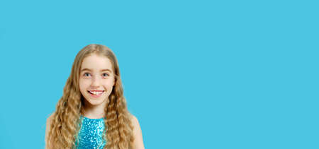 A beautiful joyful small Caucasian girl in a beautiful blue dress looks into the camera. Isolated half-length portrait on a blue background and copy space.