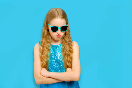 Beautiful Caucasian teenager girl looks angrily. The girl is dressed in a beautiful blue dress and sunglasses. Isolated half-length portrait on a light blue background. 版權商用圖片