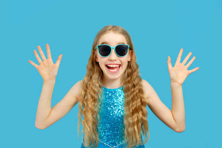 Beautiful joyful little Caucasian girl in a blue dress looks into the camera. She shows her hands and rejoices. Isolated half-length portrait on a blue background.