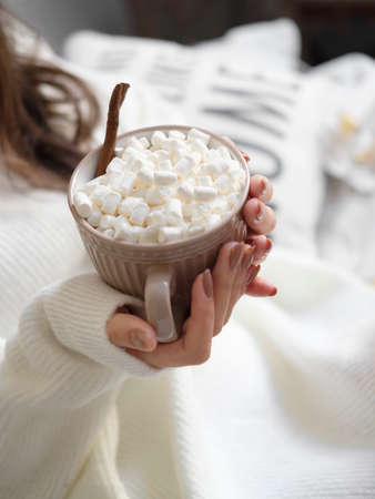 Womans hands with manicure with a cup of hot chocolate and small marshmallows.