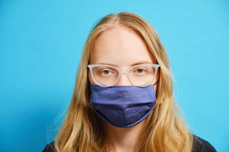 Young blonde Caucasian girl with glasses in a mask on a blue background. Studio photo and copy space. High quality photo 免版税图像