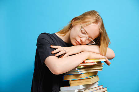 Tired Caucasian girl student laid her head and sleeps on a stack of books. Isolated half-length portrait on a light blue background.