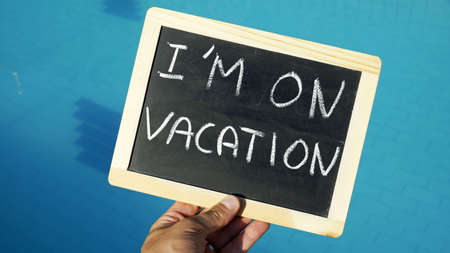 deprivation: I am on vacation written on a chalkoard at a pool