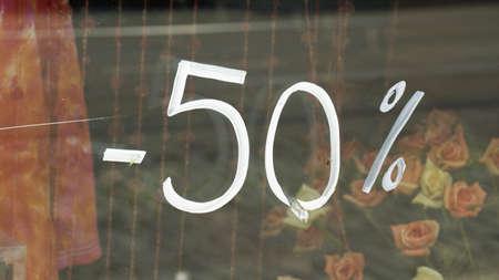 50% discount is written on a window photo