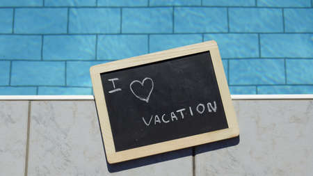 I love vacation written on a chalboard at a pool photo