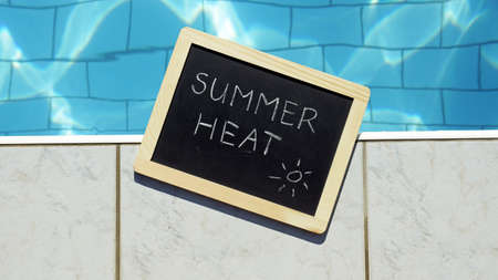 Summer heat written on a chalboard  at a pool photo