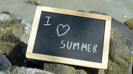 conditioned: I love the summer written on a chalkboard on the rocks Stock Photo