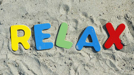 Relax written with wooden letters on the beach photo