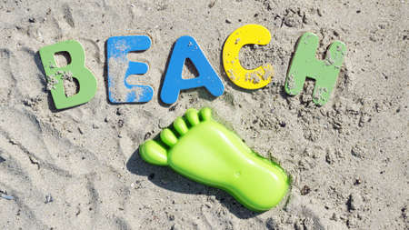 Beach written with wooden letters and a footprint on the beach photo
