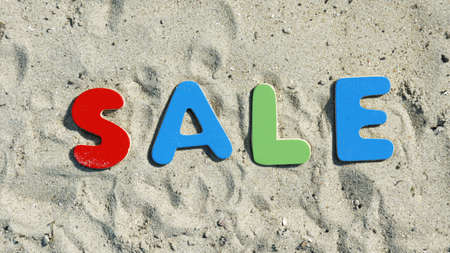 discounted: Sale in the summer written with sandy collered letters