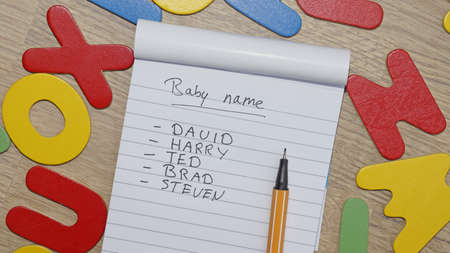 Choosing baby name for a boy written on a note, around wooden letters photo