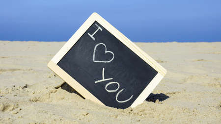 I love you written on a chalkboard on the beach                          photo