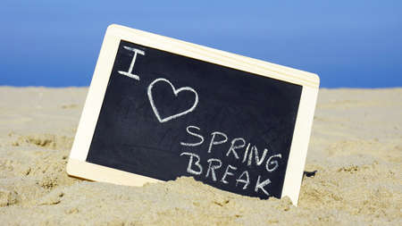eastertime: I love spring break written on a chalkboard on the beach Stock Photo