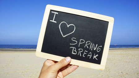 springbreak: I love spring break written on a chalkboard on the beach