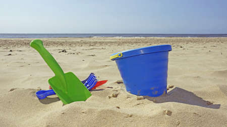 plastic shovel and bucket on the sand photo