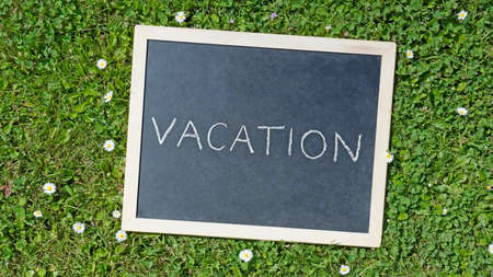 Vacation written on a board in a park with flowers photo