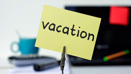 Vacation written on a memo in a office