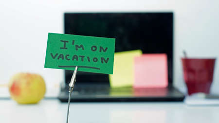 absent: I am on vacation written on a memo at the office