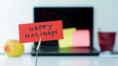 bussiness time: Happy holidays written on a memo in a office