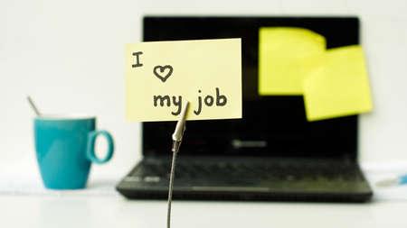 I love my job written on a memo at the office Фото со стока