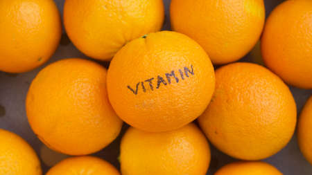 Vitamin written on  a orange Stock Photo