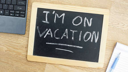 unavailable: I am on vacation written on a chalkboard at the office Stock Photo