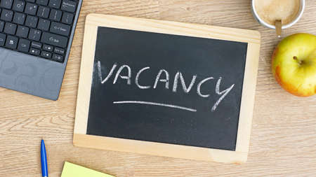 Vacancy written on a chalkboarde at the office Stock Photo