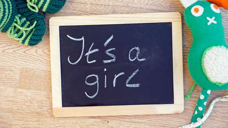 It is a girl written on a chalkboard in a baby room photo