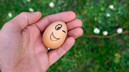 A funny egg in the nature is winking photo