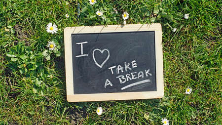 take a breather: Take a break written on a chalkboard in a park