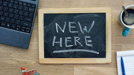 New here written on a chalkboard at the office