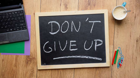 Dont give up written on a chalkboard at the office photo