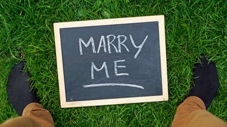 Marry me written on a chalkboard in a park photo