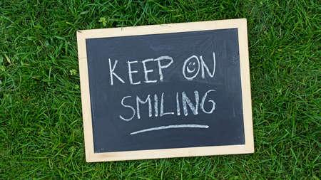Keep on smiling written on a chalkboard in the nature Reklamní fotografie
